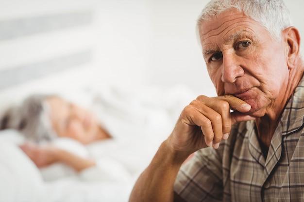 Ritratto dell'uomo senior preoccupato che si siede sul letto in camera da letto