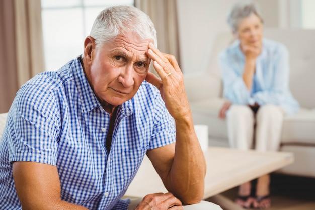 Ritratto dell'uomo senior preoccupato che si siede sul sofà in salone