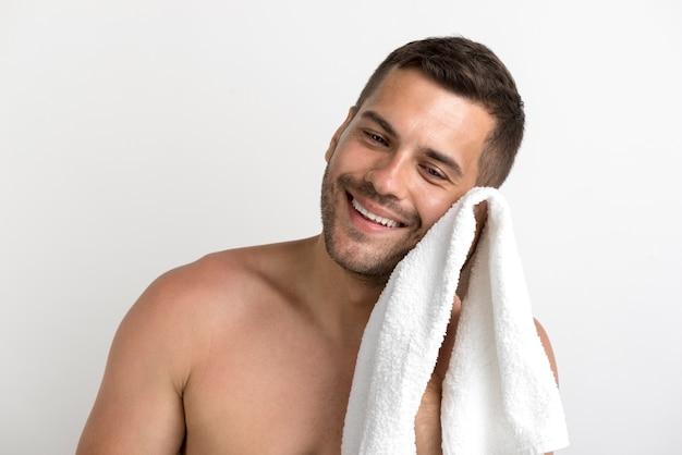 Ritratto dell'uomo senza camicia sorridente che pulisce il suo fronte con l'asciugamano bianco