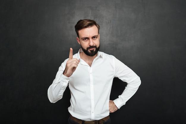 Ritratto dell'uomo serio 30s in camicia bianca che posa sulla macchina fotografica con la mostra del dito verso l'alto isolata sopra grigio scuro