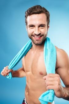 Ritratto dell'uomo sorridente che guarda macchina fotografica con l'asciugamano