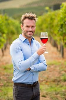 Ritratto dell'uomo sorridente che tiene bicchiere di vino rosso