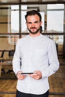 Ritratto dell'uomo sorridente che tiene compressa digitale che esamina macchina fotografica