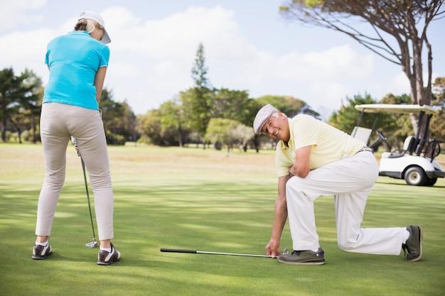 Ritratto dell'uomo sorridente del giocatore di golf dalla donna