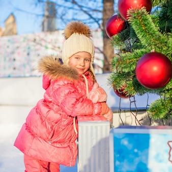 Ritratto della bambina adorabile all'albero di natale sulla pista di pattinaggio