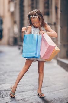 Ritratto della bambina adorabile che cammina con i sacchetti della spesa all'aperto in città europea.