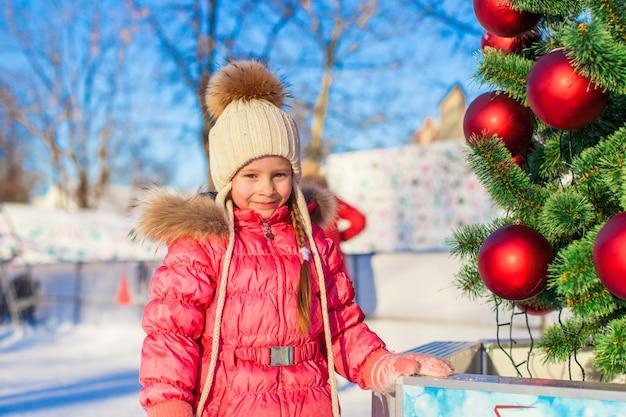 Ritratto della bambina adorabile vicino all'albero di natale sulla pista di pattinaggio