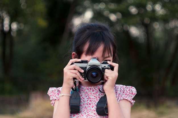 Ritratto della bambina allegra asiatica che prende foto con la macchina da presa