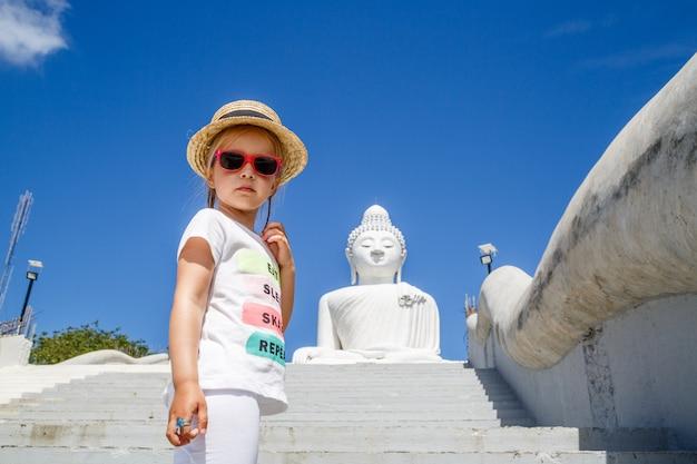 Ritratto della bambina che sta vicino alla grande statua di buddha a phuket, tailandia