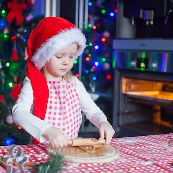 Ritratto della bambina con i biscotti del pan di zenzero di natale di cottura del matterello