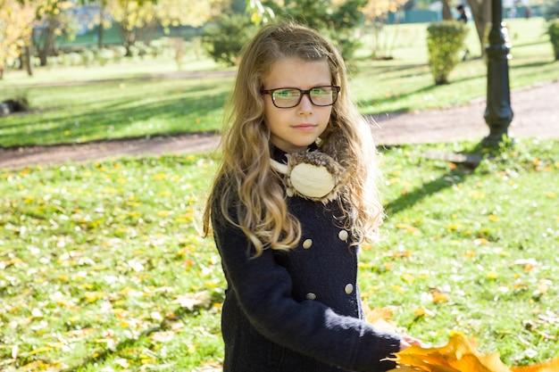 Ritratto della bambina con le foglie di acero gialle