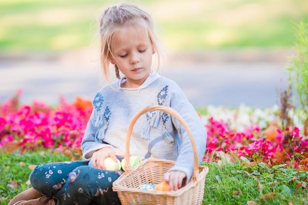 Ritratto della bambina con un canestro pieno delle uova di pasqua il giorno di molla all'aperto