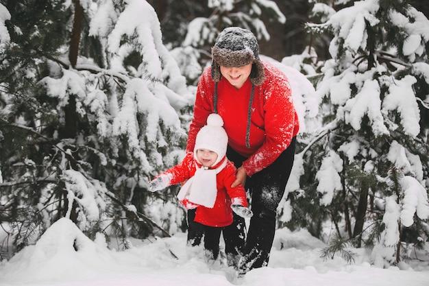 Ritratto della bambina felice in cappotto rosso con il papà divertendosi con la neve nella foresta di inverno. ragazza che gioca con il papà.