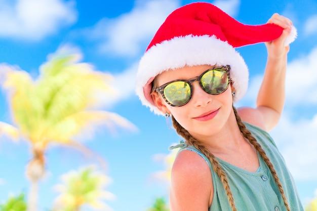 Ritratto della bambina in cappello della santa durante la vacanza della spiaggia di natale