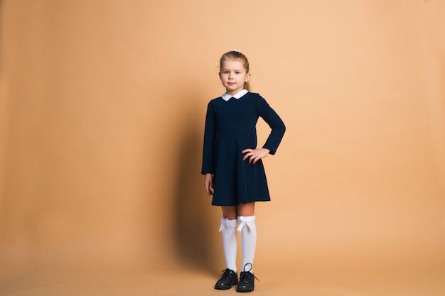 Ritratto della bambina in uniforme scolastico isolato su marrone.