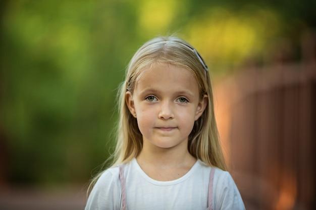 Ritratto della bambina seria con capelli biondi all'aperto