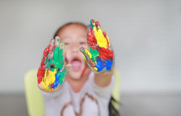 Ritratto della bambina sorridente che guarda tramite le sue mani variopinte e guancia dipinte nella stanza dei bambini.