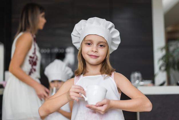 Ritratto della bambina sveglia che tiene tazza bianca in cucina