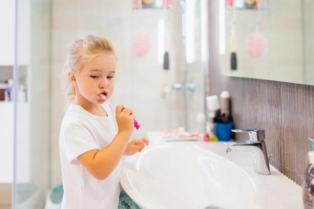 Ritratto della bambina sveglia con capelli biondi quale dente di pulizia con la spazzola e dentifricio in bagno.