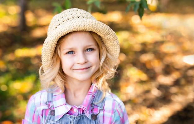 Ritratto della bambina sveglia in piccolo cappello di paglia