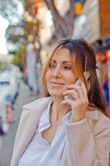 Ritratto della bella donna che sta e che parla sul telefono alla via durante il giorno.