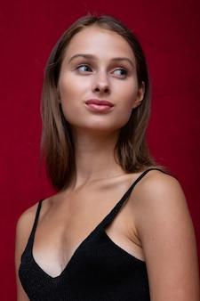 Ritratto della bella ragazza amabile con il sorriso sulla parete rossa.