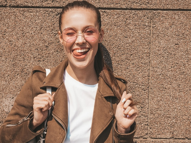 Ritratto della bellissima modella bruna sorridente vestita in abiti hipster giacca e jeans vicino al muro donna divertente e positiva sbattere le palpebre
