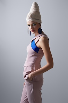 Ritratto della bellissima modella in blusa senza maniche, pantaloni e turbante sulla testa.