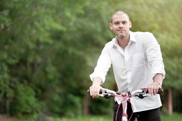 Ritratto della bici di guida del maschio adulto all'aperto