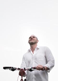 Ritratto della bici di guida del maschio adulto con lo spazio della copia
