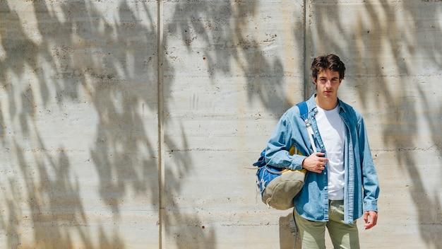 Ritratto della borsa di trasporto dell'uomo bello che esamina macchina fotografica che sta contro il muro di cemento