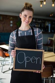 Ritratto della cameriera di bar che mostra ardesia con il segno aperto