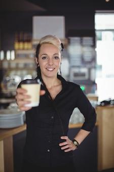 Ritratto della cameriera di bar che sta con la tazza di caffè eliminabile