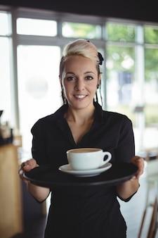 Ritratto della cameriera di bar che sta con la tazza di caffè