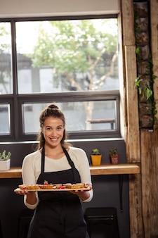 Ritratto della cameriera di bar che tiene un vassoio con i tortini