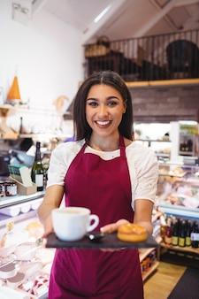 Ritratto della cameriera di bar che tiene una tazza di caffè e gli spuntini