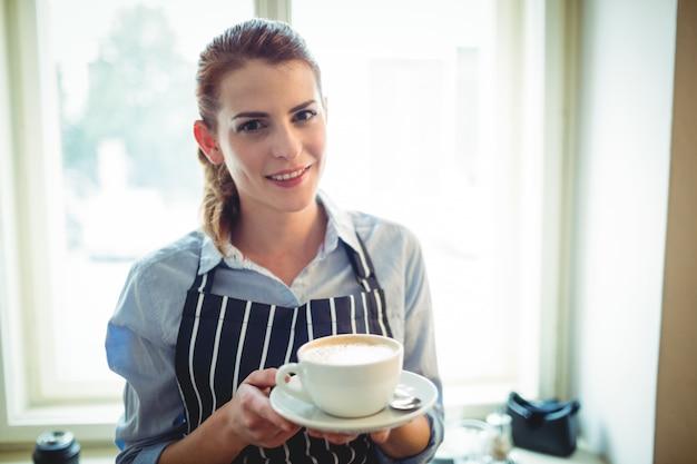 Ritratto della cameriera di bar felice che offre caffè al caffè