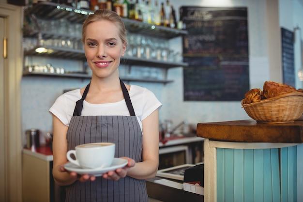 Ritratto della cameriera di bar felice che serve bevanda al caffè