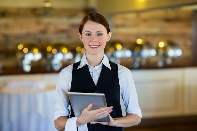 Ritratto della cameriera di bar sorridente che tiene compressa digitale