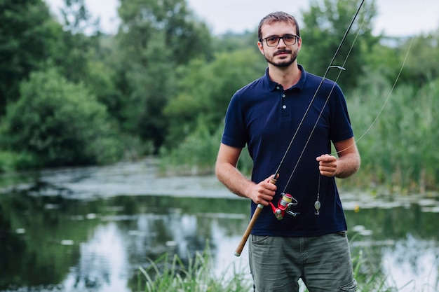 Ritratto della canna da pesca sorridente della tenuta dell'uomo vicino al lago