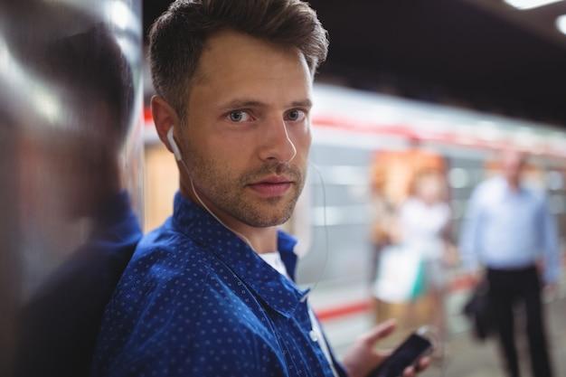 Ritratto della canzone d'ascolto dell'uomo bello sul telefono cellulare
