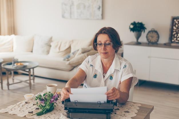 Ritratto della carta della tenuta di signora più anziana e in camicia bianca a casa durante il giorno.
