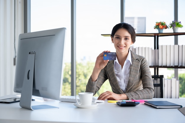 Ritratto della carta di credito della tenuta della donna di affari in ufficio moderno