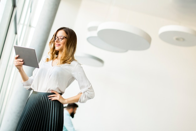 Ritratto della compressa diritta del wirth della giovane donna di affari nell'ufficio dalla finestra