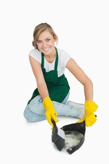 Ritratto della domestica sorridente che utilizza la spazzola e la vaschetta della polvere