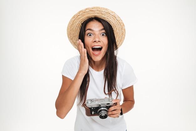 Ritratto della donna abbastanza emozionante in cappello che tiene una macchina fotografica