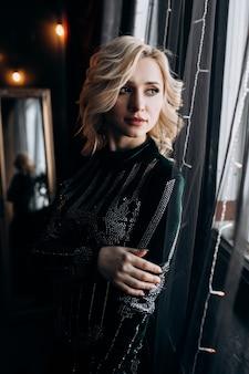 Ritratto della donna adorabile in vestito nero che posa in una stanza scura accogliente con la decorazione di natale