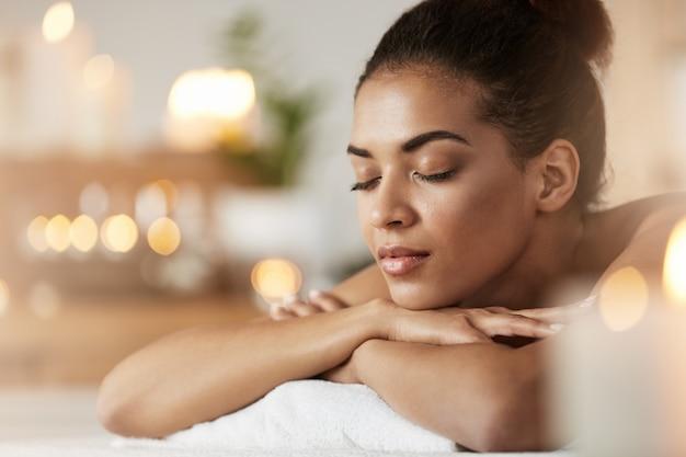 Ritratto della donna africana tenera con gli occhi chiusi che riposano rilassamento nel ricorso di stazione termale.