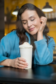 Ritratto della donna alla moda che tiene cioccolata calda