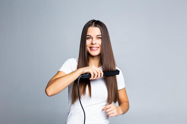 Ritratto della donna allegra che usando raddrizzatore per i suoi capelli ricci che preparano per la pettinatura facile comoda di festa della data di evento isolata su gray